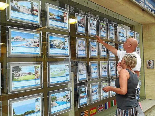 Couple looking at rental prices in Minorca estate agent window.