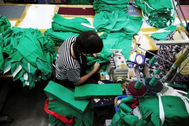 """A woman works on tracksuits inspired by Netflix series """"Squid Game"""" at a clothing factory in Seoul."""
