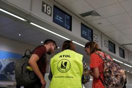 An ATOL official assists passengers at Malta International Airport