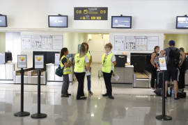 Passengers are seen at Thomas Cook check-in points at Minorca airport