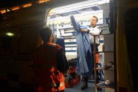 A docotor is getting dressed inside an ambulance.