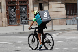 A biker wearing a Deliveroo backpack drives in the central Barcelona, Spain.