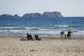 A family poses for a picture next to the sea in Paguera beach