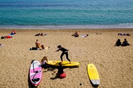 A person teaches surfing to children at Barceloneta beach