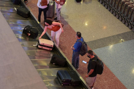 Travelers wait for luggage at an airport