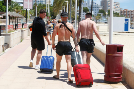 Tourists carry their luggage at Magaluf beach
