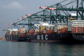 Cargo ships are docked beside cranes at the MSC container terminal at the port of Valencia
