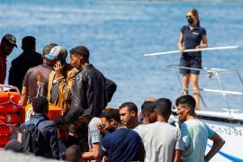 Migrants wait to disembark from a Spanish coast guard vessel.