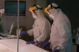 EFM operatives wear protective suits to treat coronavirus corpses.
