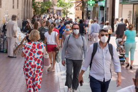 People walking through the streets of Palma wearing masks