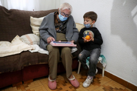 Florentina Martin, a 99 year-old woman who survived coronavirus disease (COVID-19), plays a digital puzzle with her great-grandson Pedro Valle at her home in Pinto