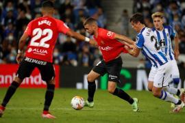 Dani Rodríguez having his shirt pulled during Mallorca's match against Sociedad