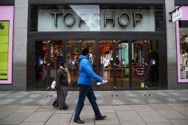 People walk past an entrance to the Topshop store at the Oxford Street, in London